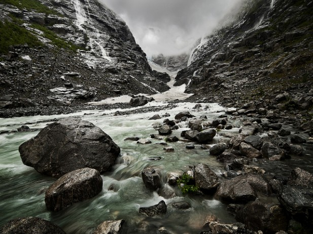 Foto de água a correr sob pedras em Kjenndalsbreen, Noruega.
