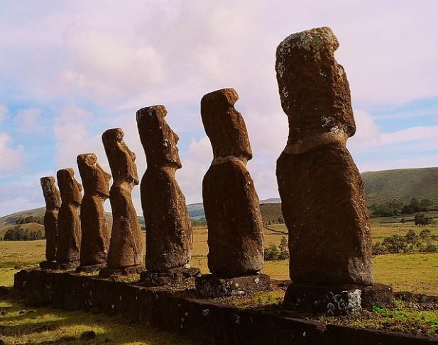 Foto de vários Moai da Ilha da Páscoa de costas.