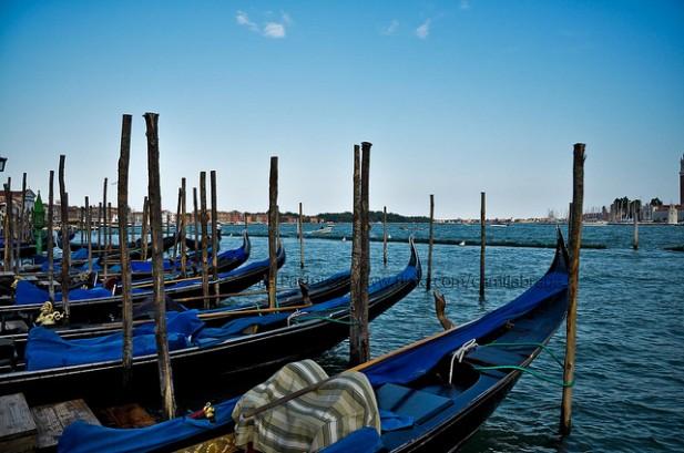 Foto panorâmica com gôndolas e Veneza ao fundo.