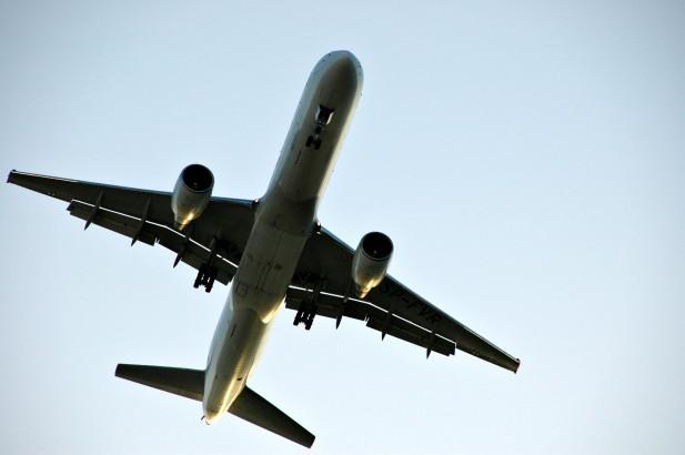 Foto de avião a voar visto por baixo.