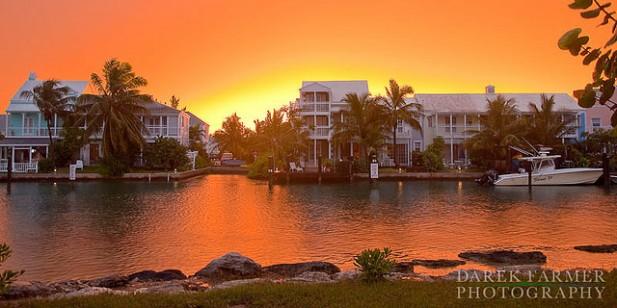 Foto de pôr-do-sol com casas e água nas Bahamas.