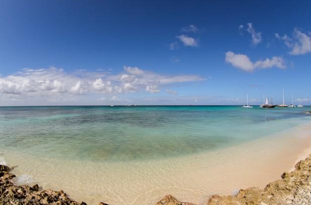 Foto de água azul do mar, com rochas e iates.