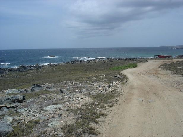 Foto de estrada com mar ao fundo.