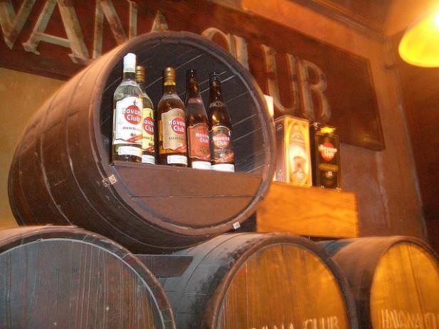 Foto de garrafas dentro de pipos no Rum Factory de Havana.