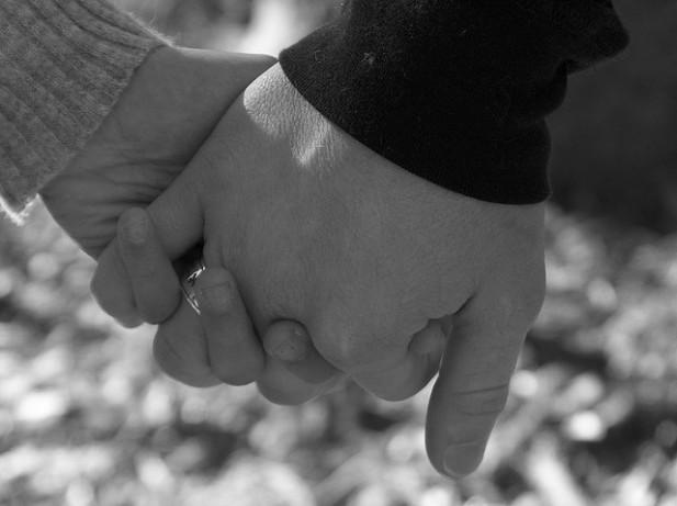 Foto a preto e branco de mãos juntas.