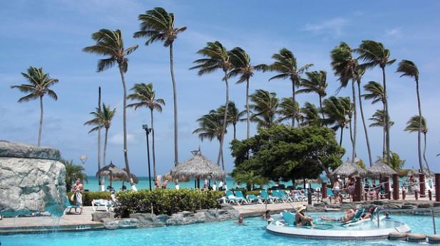 Foto de piscina, palmeiras, pessoas e praia ao fundo.