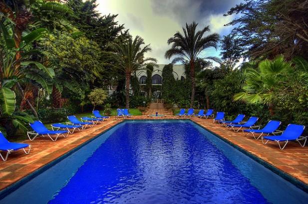 Foto de piscina de hotel com espreguiçadeiras azuis e palmeiras à volta.