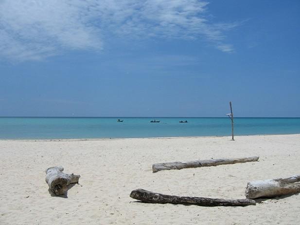 Foto de areia e mar com pescadores no Haiti.