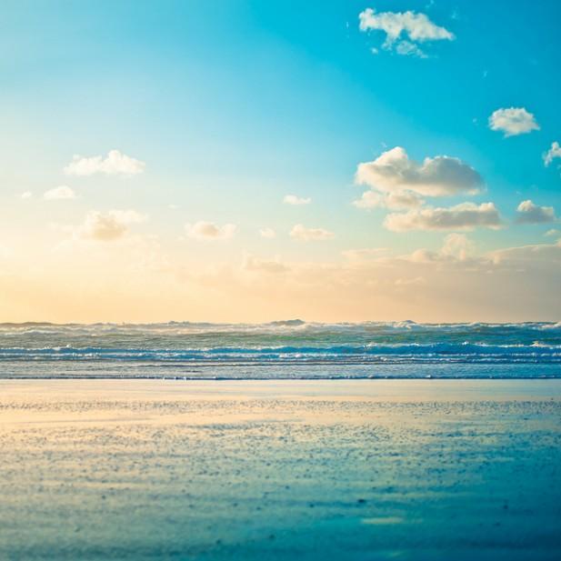 Foto de areia, mar e horizonte azul.