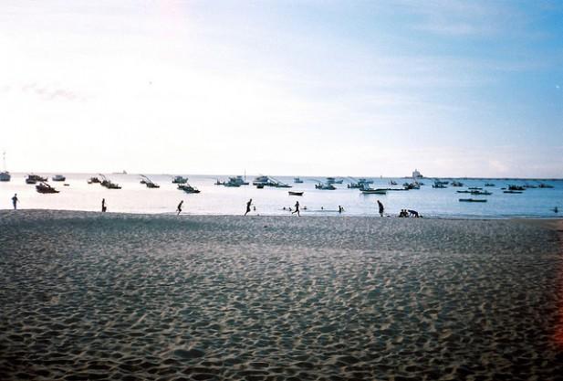 Foto de praia de Mucuripe com areia e vários barcos no mar.