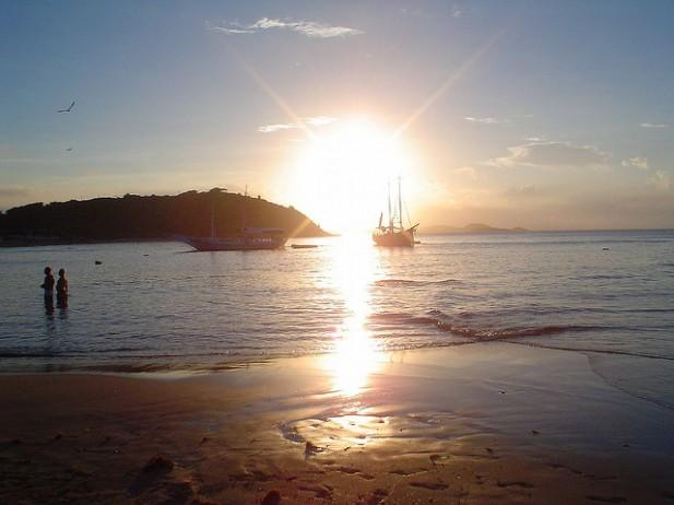 Foto do pôr-do-sol com mar e barco em Búzios, Brasil.