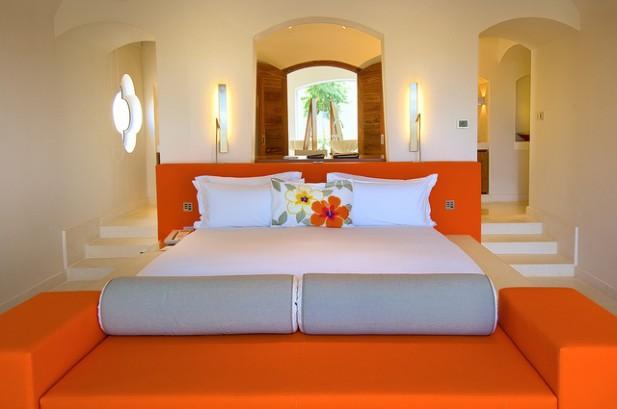 Foto de quarto de hotel iluminado com laranjas e paredes brancas.