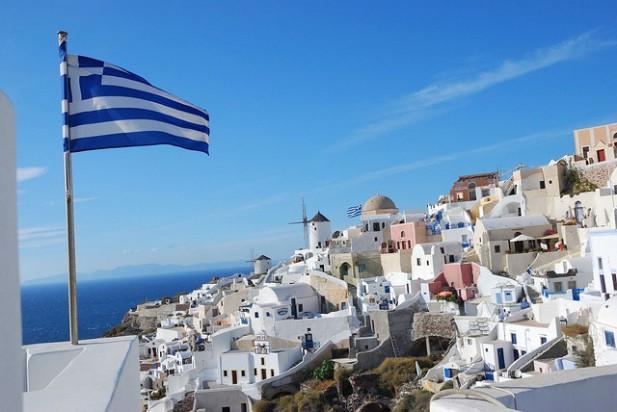 Foto de vila de Santorini com vila e bandeira da Grécia.