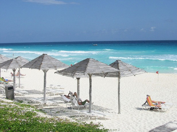 Foto de praia, mar e espreguiçadeiras, em Cancún, México.