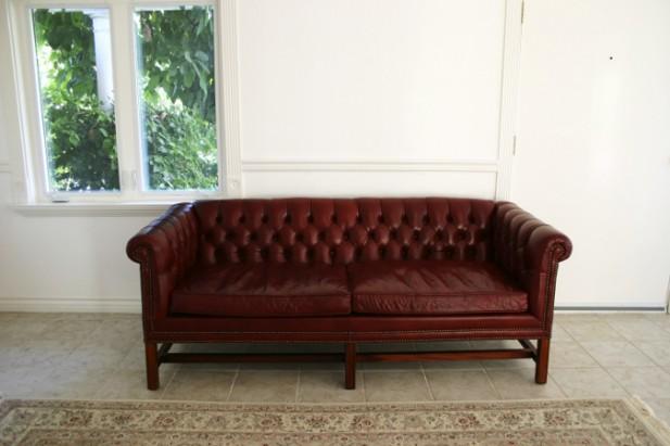 Foto de um sofá vermelho com paredes brancas e uma janela.
