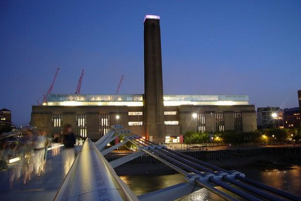 Foto à noite de ponte com o museu de Londres Tate Gallery of Modern Art ao fundo.