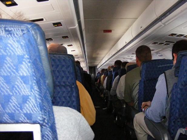 Foto do interior de um avião com pessoas sentadas nas cadeiras.