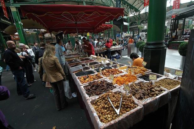 Foto de banca de venda com frutos e pessoas à volta.