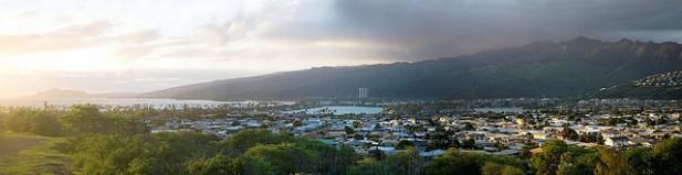 Foto panorâmica com cidade e montanhas.