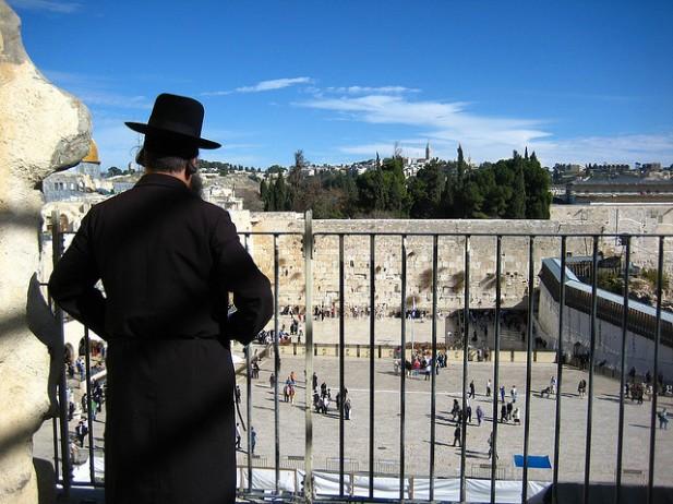 Foto de pessoa à varanda e pessoas em frente ao Muro das Lamentações.