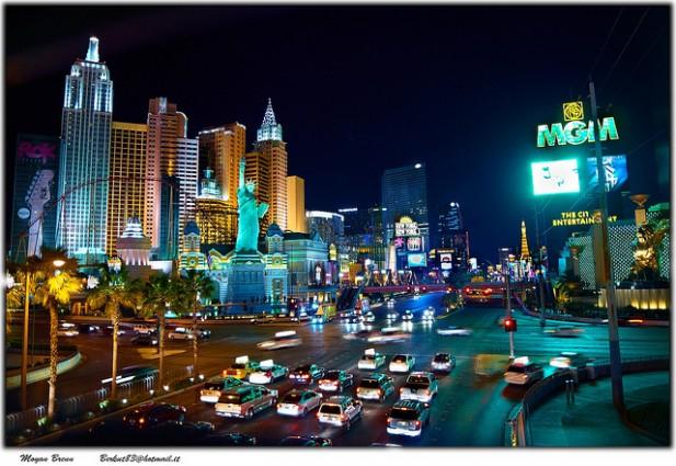Foto de cidade à noite com carros e edifícios.