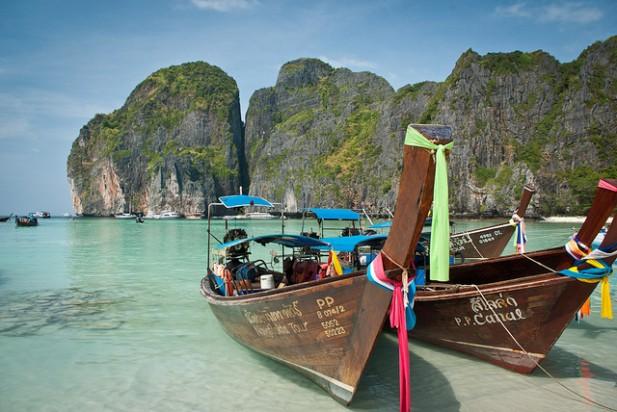 Foto de água, montanhas e barcos na areia.