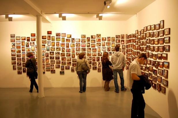 Foto de pessoas a ver fotos em parede.
