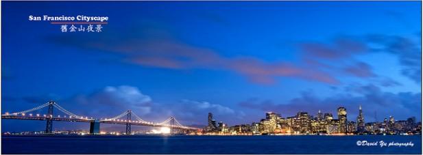 Foto de ponte e prédios à noite.