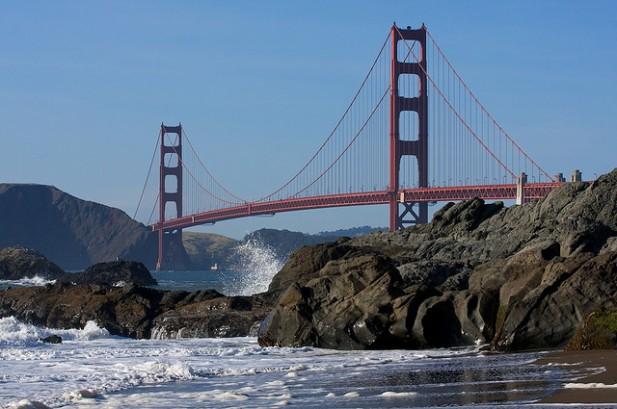Foto de ondas, rochas e ponte.