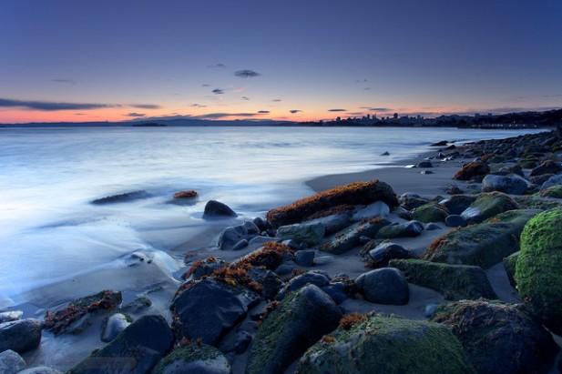 Foto de praia, ondas, areia e pedras ao amanhecer.