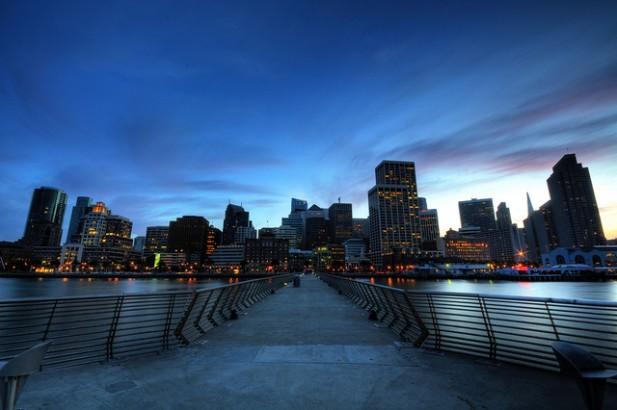 Foto de ponte, rio e prédios à noite.