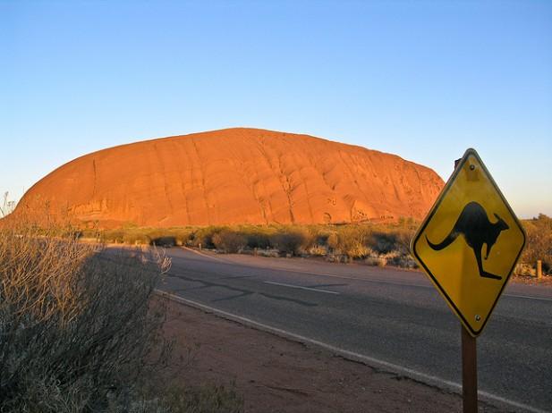Foto de estrada, placa de kangurus e montanha.