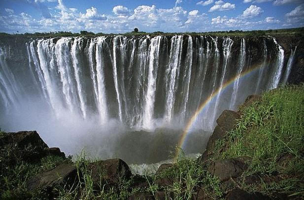 Foto de quedas de água com arco-íris à frente.