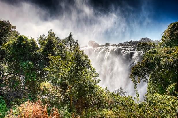 Foto de vegetação, nevoeiro e queda de água ao fundo.