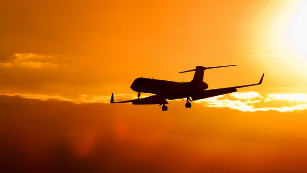 Foto de avião com pôr-do-sol atrás.