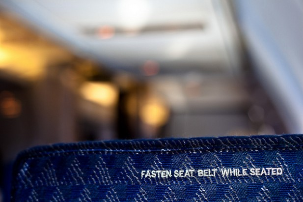 Foto de banco com o 'Fasten Seat Belt While Seated' em grande plano.