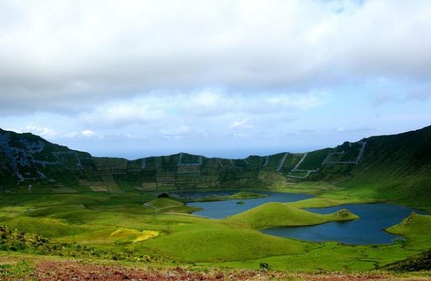 Foto de lagoa com montanhas em redor e nuvens.