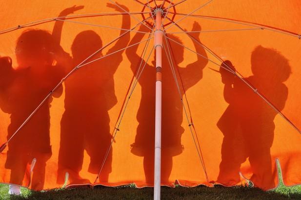 Foto de crianças a brincar atrás de guarda sol cor de laranja.