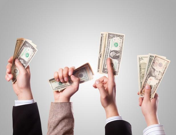 Foto de várias pessoas a licitar com dinheiro na mão.