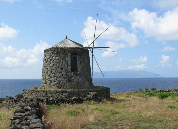 Foto de moinho de vento com mar ao fundo.