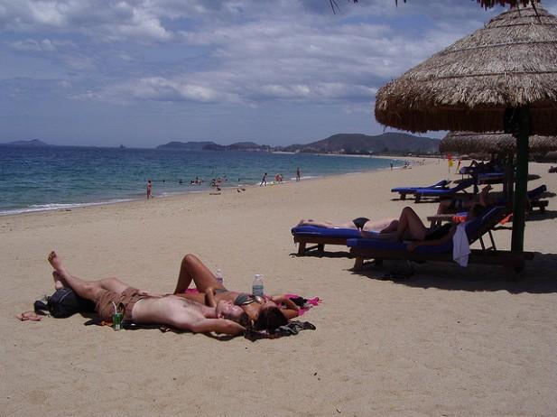 Foto de pessoas a apanhar sol na praia.