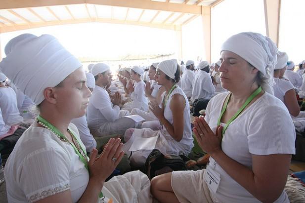 Foto de várias mulheres juntas e vestidas de branco a meditar.