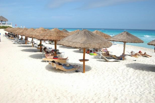 Foto de praia, com guarda-sóis, areia branca e mar azul.