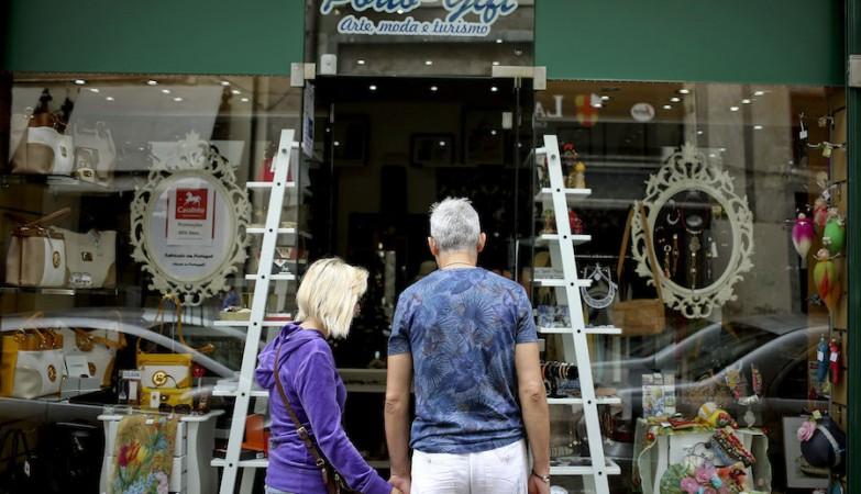 Um casal de turistas observa a montra da Porto Gift, uma das muitas lojas de lembranças que surgiram no Porto com o aumento de visitantes